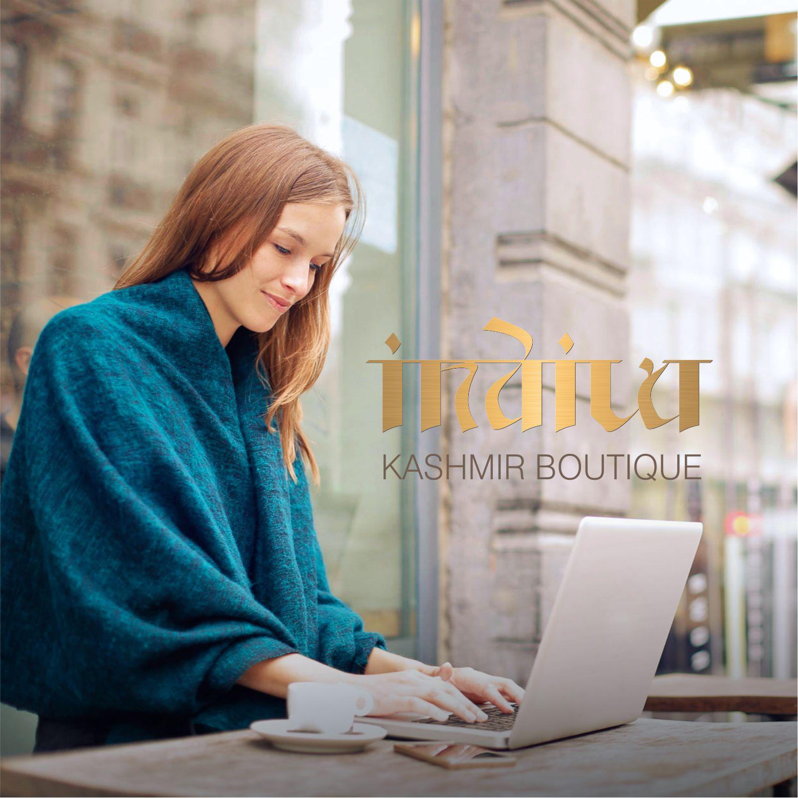 O-ZEN Design Portfolio Indiva Kashmir Online Shop - Frau sitzt am Tisch mit Laptop und hat ein Kashmir Schal über die Schultern